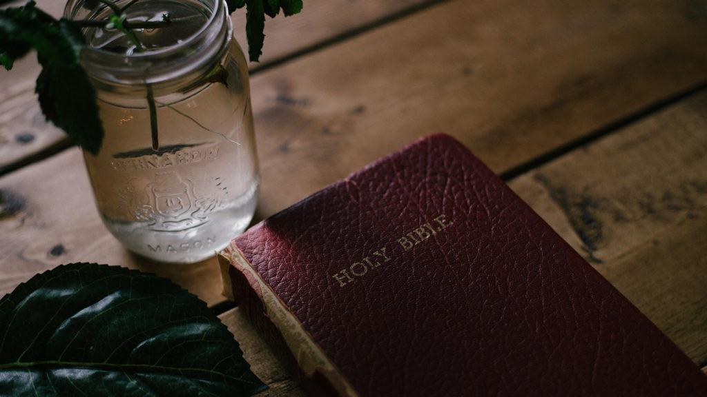 Holy-Bible-beside-clear-mason-jar-on-table
