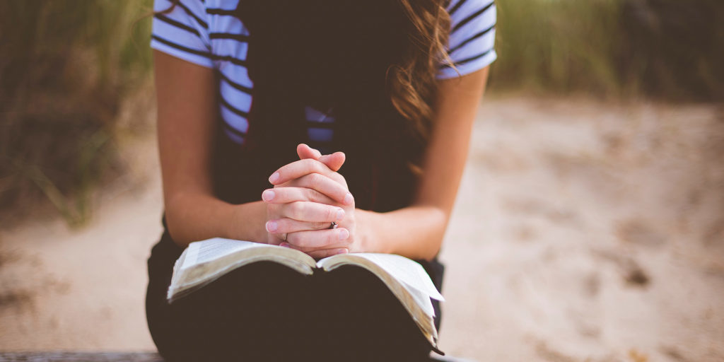 woman-sitting-on-brown-bench-while-reading-book-and-praying
